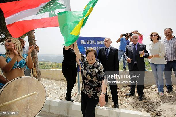 A woman waves a Brazilian flag in front of a plaque reading in Portuguese and Arabic 'Street Michel Temer Vice President of Brasil' during a...
