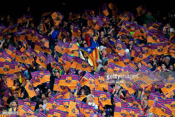 TOPSHOT A woman waves a Catalan proindependence Estelada flag among Barcelona flags during the Spanish league football match between FC Barcelona and...
