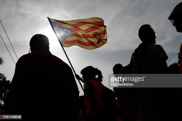 A woman waves a Catalan proindependence Estelada flag as people gather during a proindependence demonstration in Barcelona marking the National Day...