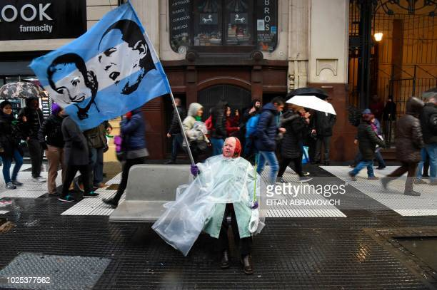Woman waves a flag depicting Argentine three-time president Juan Domingo Peron and his wife Eva Peron, during a march for teachers' salary increase...