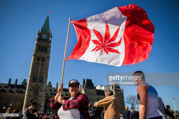 A woman waves a flag with a marijuana leef on it next to a group gathered to celebrate National Marijuana Day on Parliament Hill in Ottawa Canada on...