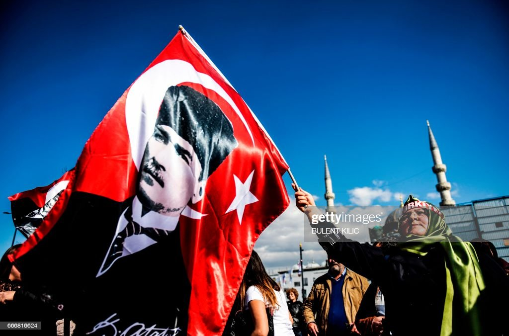TOPSHOT - A woman waves a flag with a portrait of the founder of modern Turkey Mustafa Kemal Ataturk in Istanbul on April 10, 2017. The Turkish public will vote on April 16, 2017 on whether to change the current parliamentary system into an executive presidency. /