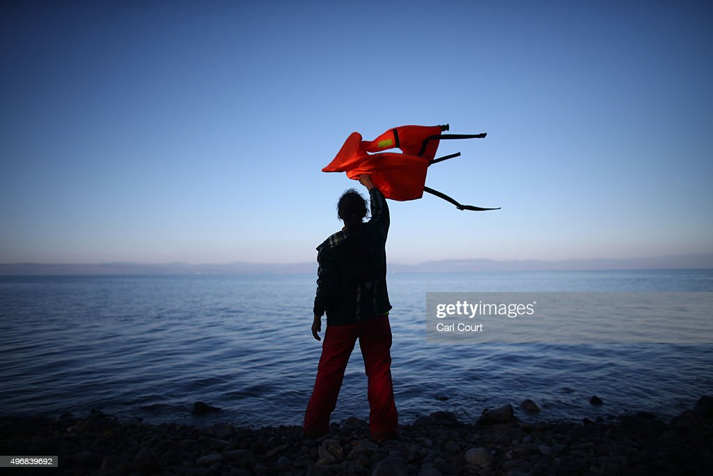 A woman waves a life jacket to direct a migrant boat ashore as it makes the crossing from Turkey to the Greek island of Lesbos on November 12, 2015 in Sikaminias, Greece. Rafts and boats continue to make the journey from Turkey to Lesbos each day as thousands flee conflict in Iraq, Syria, Afghanistan and other countries. Over 500,000 migrants have entered Europe so far this year and approximately four-fifths of those have paid to be smuggled by sea to Greece from Turkey, the main transit route into the EU. Most of those entering Greece on a boat from Turkey are from the war zones of Syria, Iraq and Afghanistan.