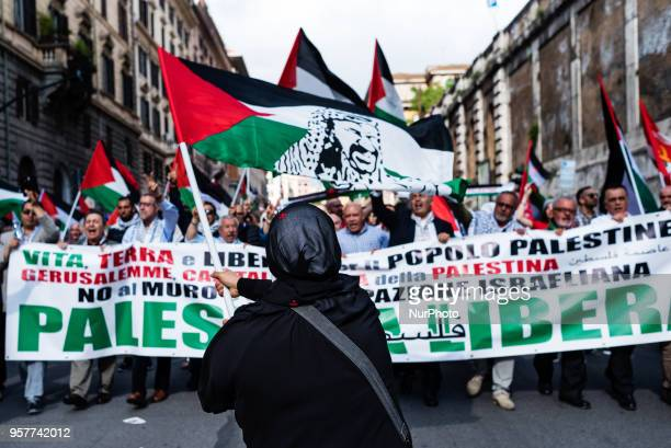 A woman waves a Palestinian flag with Asser Arafat face at a proPalestine rally in Rome Italy on May 12 2018 The Palestinian community in Italy...