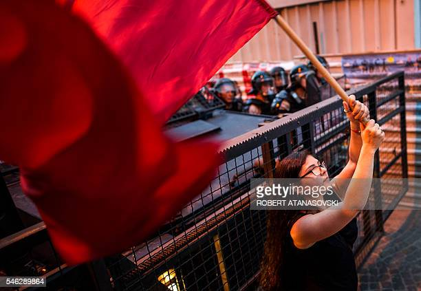 A woman waves a red flag in front of a police cordon during an antigovernment protest in Skopje on July 11 in a series of protests dubbed Colourful...