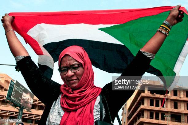 A woman waves a Sudanese national flag during a mass demonstration near the presidential palace in the capital Khartoum on September 12 as protesters...