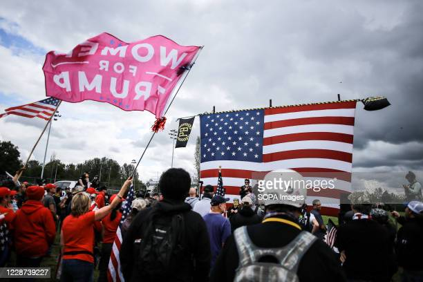 """Woman waves a """"Women For Trump"""" flag in the crowd of the Proud Boys rally. Hundreds of members of the far-right group Proud Boys arrived at Delta..."""