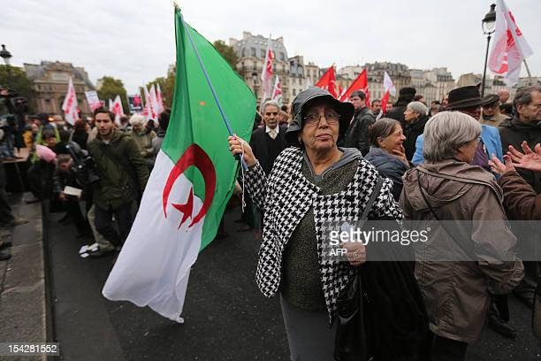 A woman waves an Algerian national flag on October 17 on the SaintMichel Bridge in Paris during a rally to commemorate a demonstration by proNational...