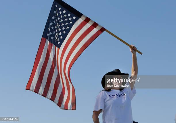 A woman waves an American flag while Air Force One with US President Donald Trump and First Lady Melania Trump taxi to parking at McCarran...