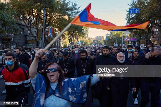 Woman waves an Armenian flag as protesters march to demand the removal of Armenian Prime Minister Nikol Pashinyan from office near the Armenian...