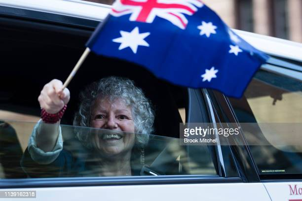 A woman waves an Australian flag during the ANZAC Day March on April 25 2019 in Sydney Australia Australians commemorating 104 years since the...