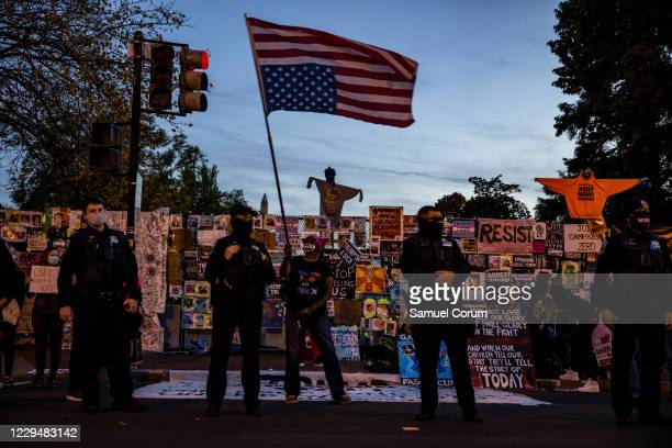 Woman waves an upside down American flag as people gather at Black Lives Matter Plaza as they wait for the results of the presidential election...