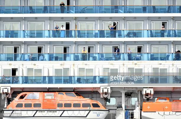 A woman waves as others look out from aboard the Grand Princess cruise ship operated by Princess Cruises as it maintains a holding pattern about 25...