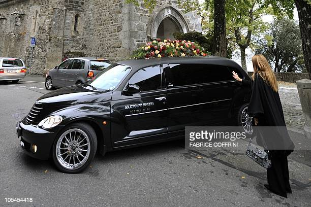 A woman waves as the hearse leaves after a private funeral service held for legendary Australian opera singer Dame Joan Sutherland in the western...