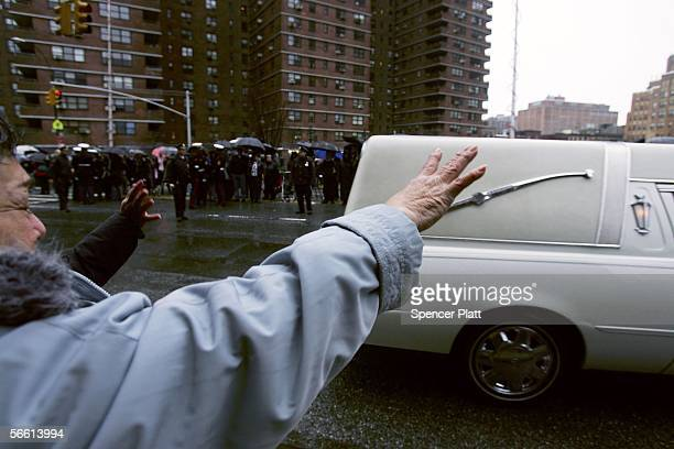 A woman waves at the hearse carrying the body of Nixzmary Brown after her funeral January 18 2006 in New York City Brown was found beaten to death...