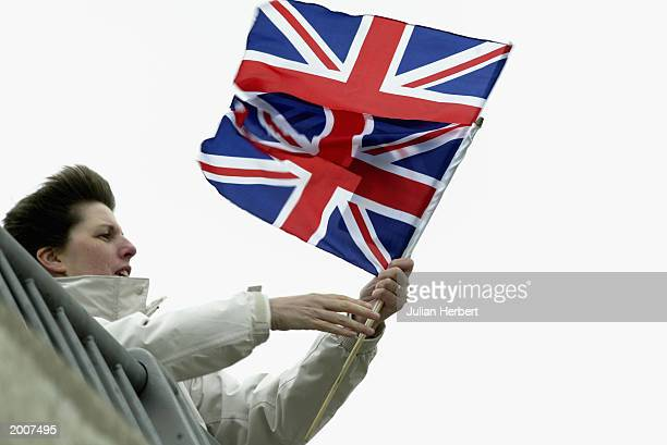 A woman waves British flags as the aircraft carrier HMS Ark Royal returns to her base 126 days after she set sail May 17 2003 in Portsmouth England...