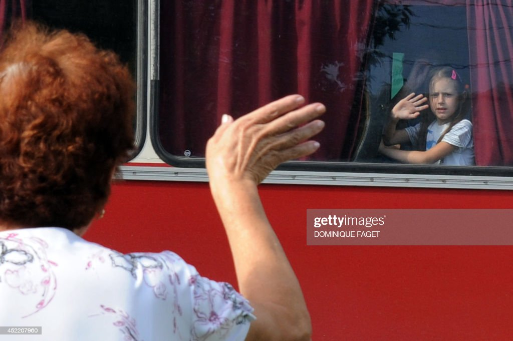 A woman waves goodbye to members of her family leaving for Russia on July 16, 2014 in Donetsk. EU leaders meet on Wednesday to decide on new sanctions against Russia and pro-Moscow separatists in east Ukraine as Kiev raises fears of an imminent invasion by thousands of Russian troops. Thousands of panicked refugees are flooding highways and packed trains heading out of the main remaining rebel strongholds in eastern Ukraine fearing attacks by government forces who lost 30 soldiers to defiant militants.