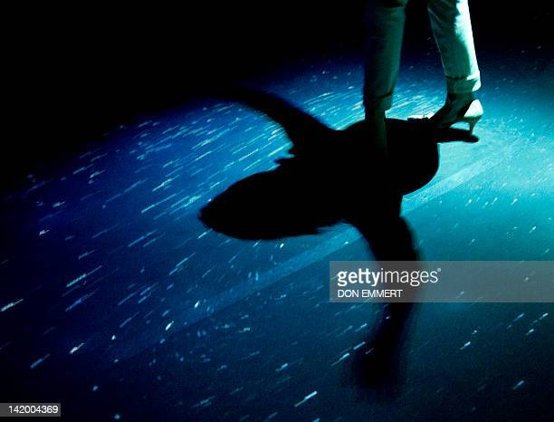 A woman waves her arms as she stands on a display as part of the Creatures of Light Nature's Bioluminescence exhibit March 27 2012 at the American...