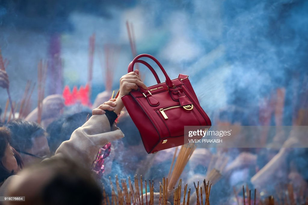 A Woman Waves Her Handbag In Circles Over Burning Incense For Good Luck During Lunar New