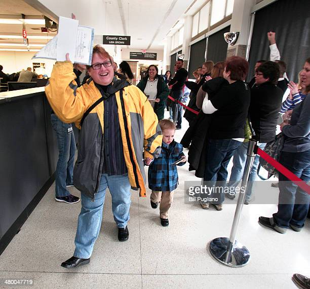 A woman waves her marriage license at the Oakland County Courthouse on March 22 2014 in Pontiac Michigan A Federal judge overturned Michigan's ban on...