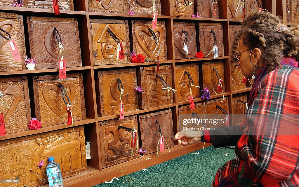 A woman waves incense in front of hand carved caskets at the African