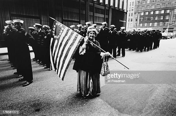 A woman waves the 'Betsy Ross' American flag in front of US Marines at the 'Home With Honor' parade to mark the homecoming of American troops from...