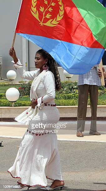 A woman waves the Ethiopian flag as Sudanese President Omar alBashir receives President of Eritrea Isaias Afewerki at Khartoum airport on May 26 2010...