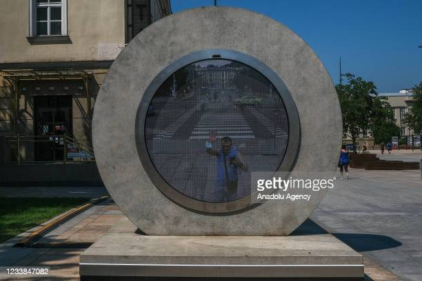 Woman waves to a real-time video portal connecting Lublin and Vilnius at the Lithuanian square on July 07, 2021 in Lublin, Poland. The virtual bridge...