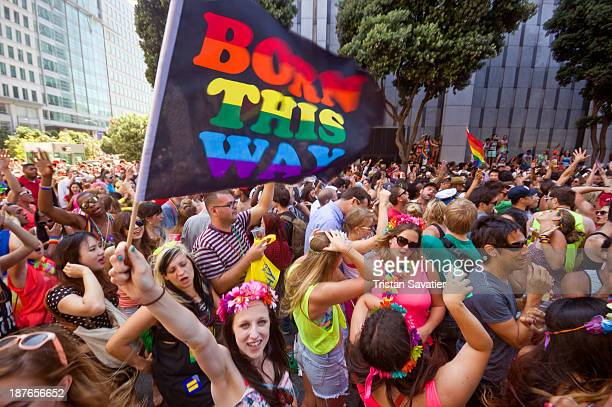 "Woman waving a ""Born this Way"" rainbow flag over the dancing crowd in front of the San Francisco Federal Building, at the Gay Pride Festival. Other..."