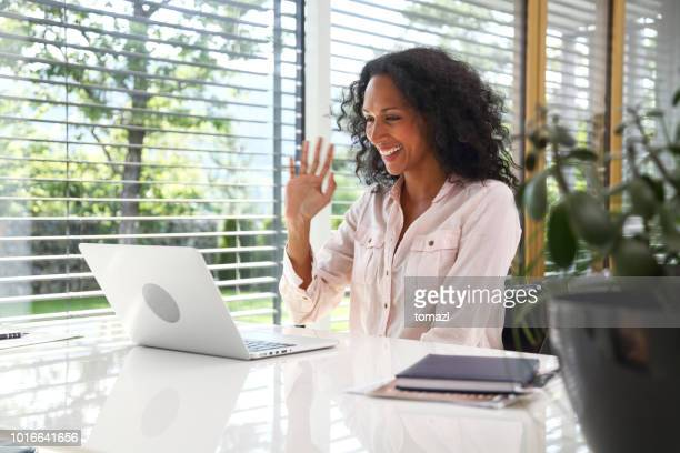 woman waving at laptop in the middle of a video conference call - virtual meeting stock pictures, royalty-free photos & images