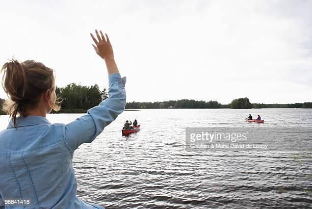 woman waving at people in canoes - mensch im hintergrund stock-fotos und bilder