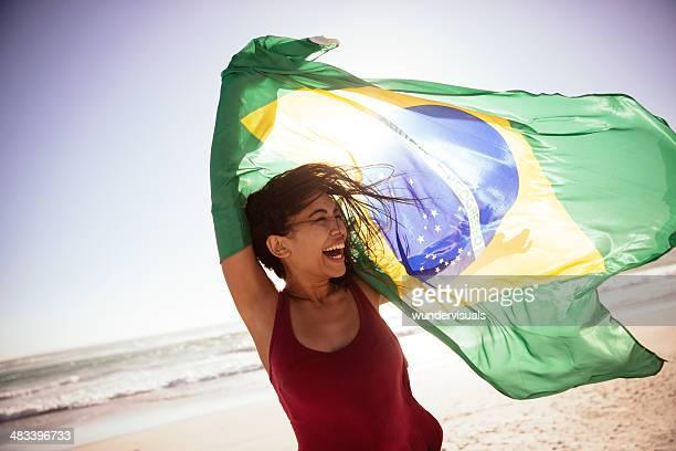 Mulher a agitar Bandeira Brasileira na praia