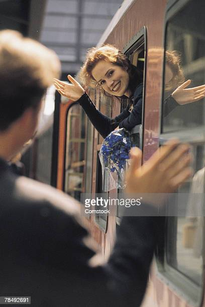 woman waving from train - long distance relationship stock pictures, royalty-free photos & images
