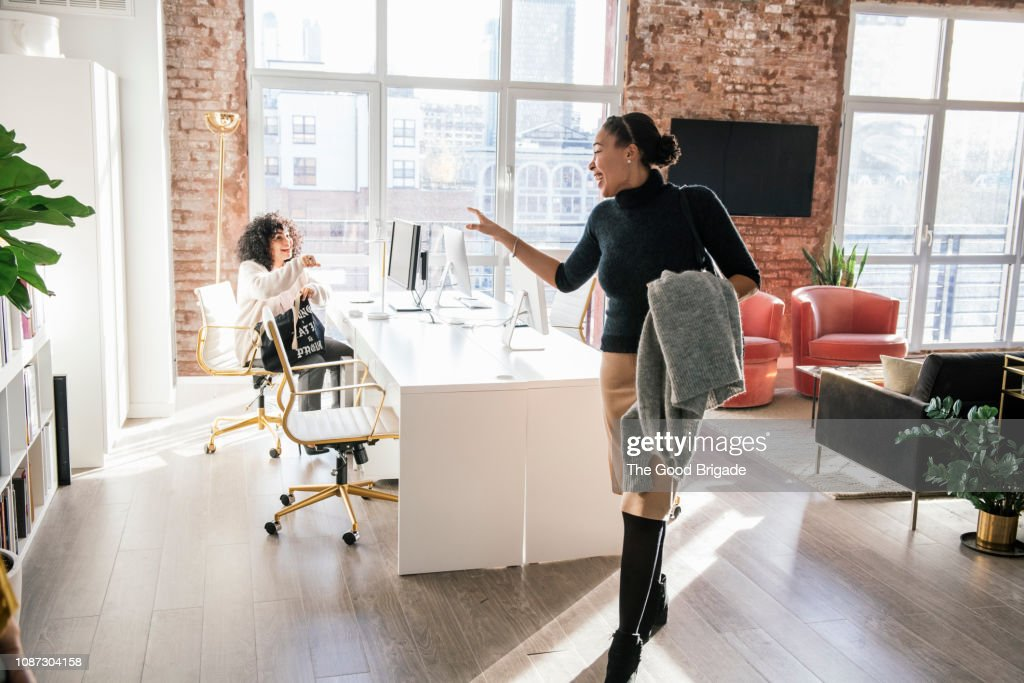 Woman waving goodbye to colleague in office : Photo
