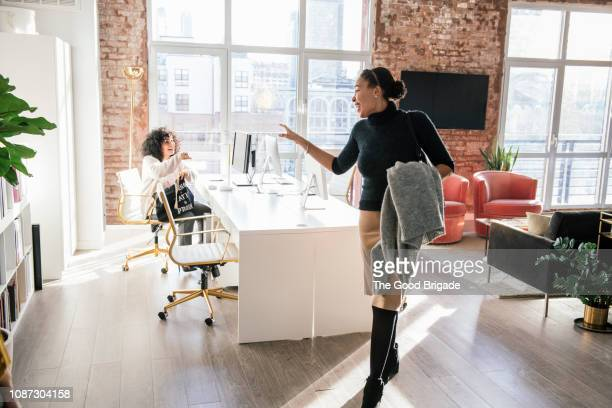 woman waving goodbye to colleague in office - leaving photos et images de collection