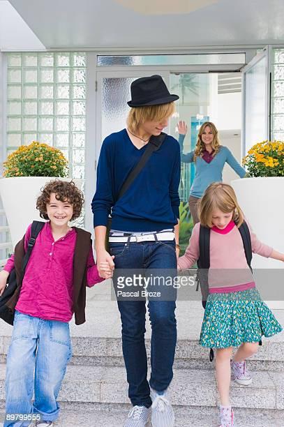 Woman waving goodbye to her children