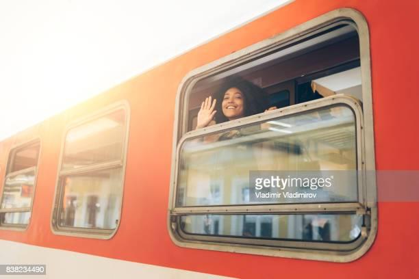 Woman waving hand through train window