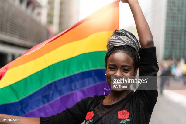 woman waving rainbow flag at gay parade - pride flag stock pictures, royalty-free photos & images