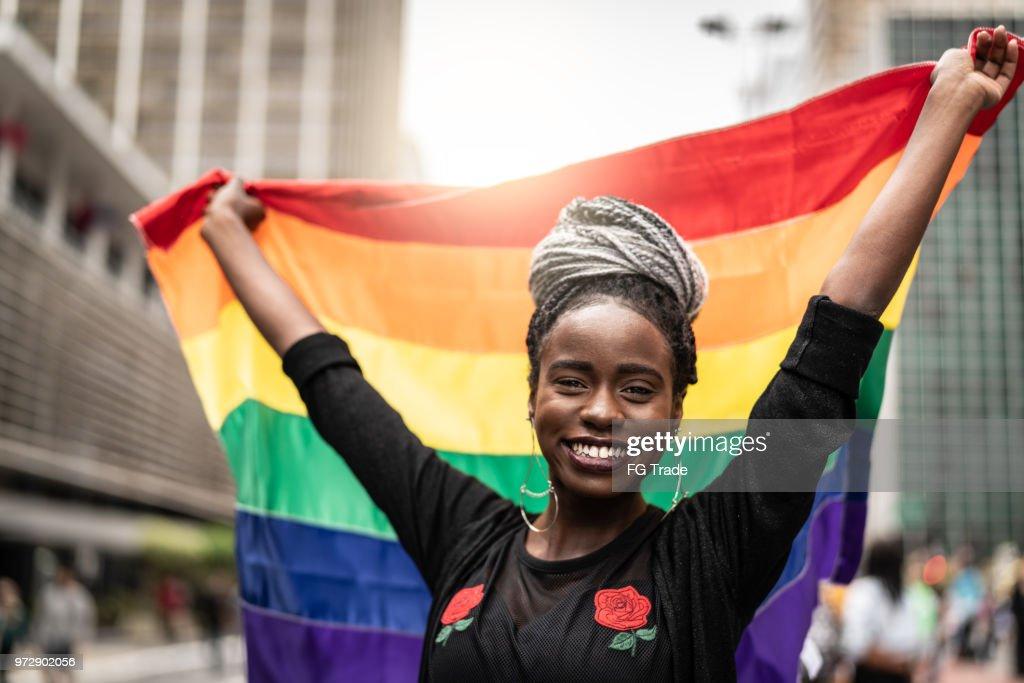 Mulher acenando a bandeira do arco-íris na parada Gay : Foto de stock