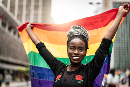 Woman Waving Rainbow Flag at Gay Parade - gettyimageskorea