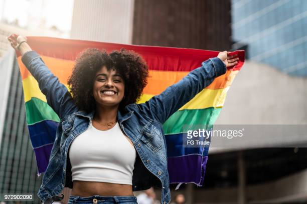 woman waving rainbow flag at gay parade - pride stock pictures, royalty-free photos & images