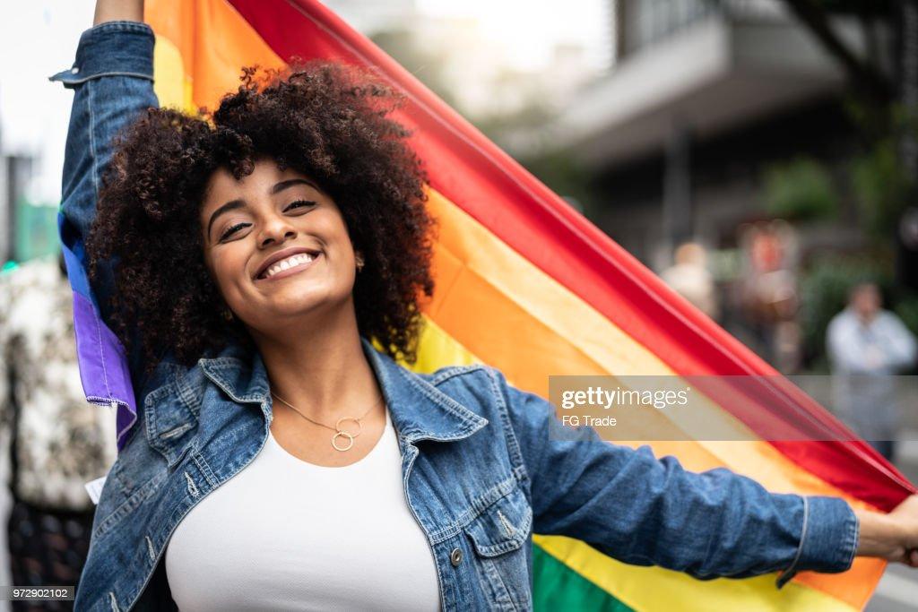 ゲイパレードに虹の旗を振っている女性 : ストックフォト
