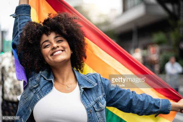 woman waving rainbow flag at gay parade - lgbtqi pride event stock pictures, royalty-free photos & images