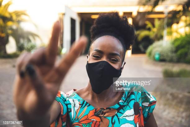 donna che saluta un amico evitando strette di mano e abbracci - afro americano foto e immagini stock