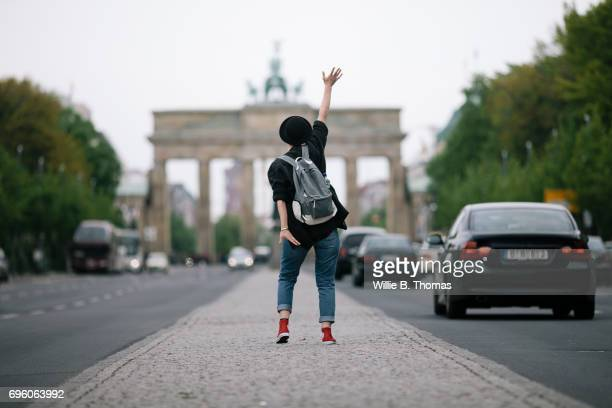 A Woman Waving To Brandenburg Gate