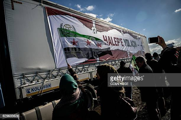 A woman wawes a free syrian flag as trucks part of an aid convoy to Aleppo organized by IHH Humanitarian Relief Foundation are leaving on December 14...