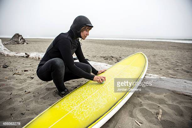 Woman waxing surfboard in the sand.