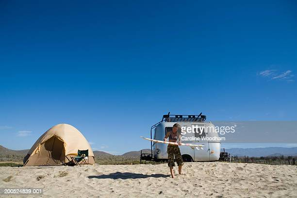 woman waxing surfboard on beach, with caravan and tent in background - brazilian waxing stock photos and pictures