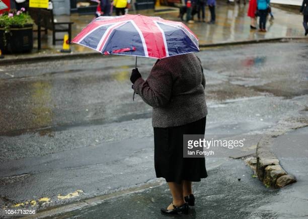 A woman wearing 1940's period clothing and carrying a Union Flag umbrella crosses a road in Pickering during the North Yorkshire Moors Railway 1940's...