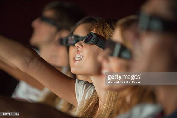 Woman wearing 3-D glasses in movie theater, arm reaching out